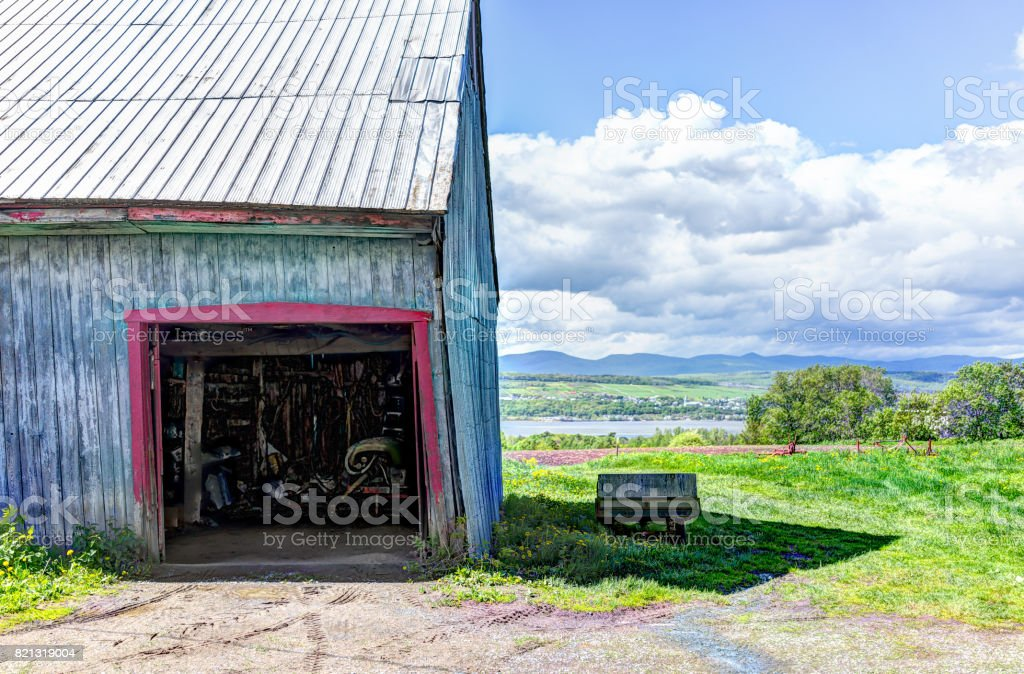 Blue painted old vintage shed overlooking river in summer landscape field in countryside stock photo