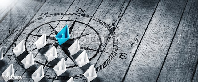 Blue Paper Boat Leading A Fleet Of Small White Boats With Compass Icon On Wooden Table With Sunlight - Leadership Concept