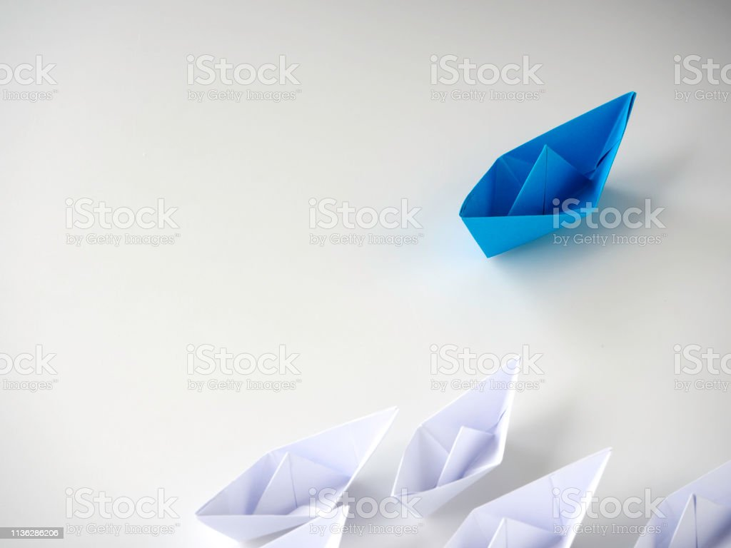 Set of origami boats. Blue paper boat leading among white ships on...
