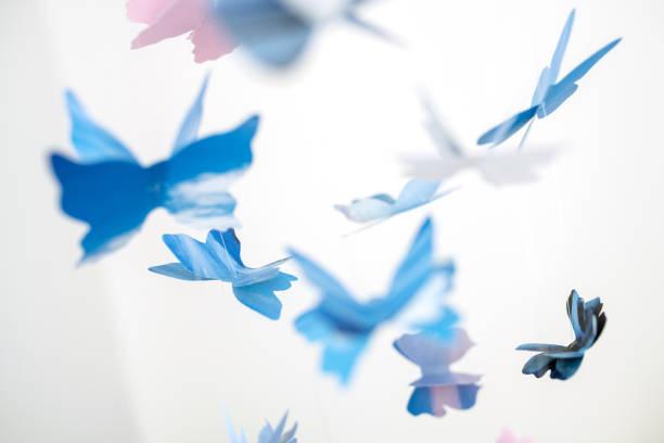 blaues papier schmetterlinge auf einem mobilen, deutschland - origami mobil stock-fotos und bilder