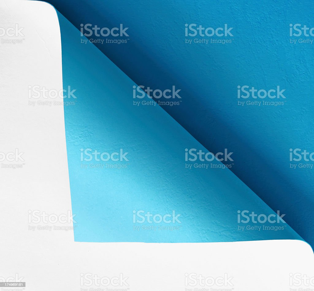 Blue paper folded over and curled stock photo