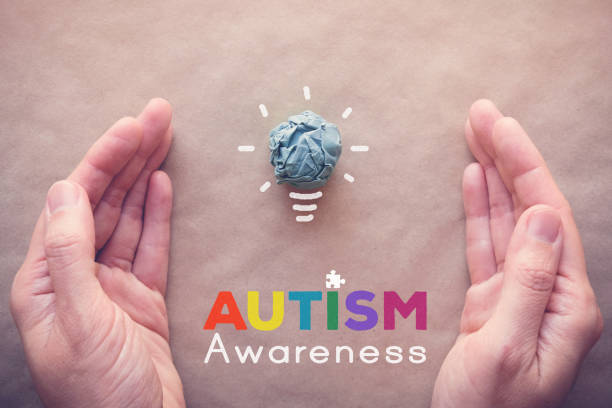 Blue paper light bulb and puzzle with hands, world Autism awareness day stock photo