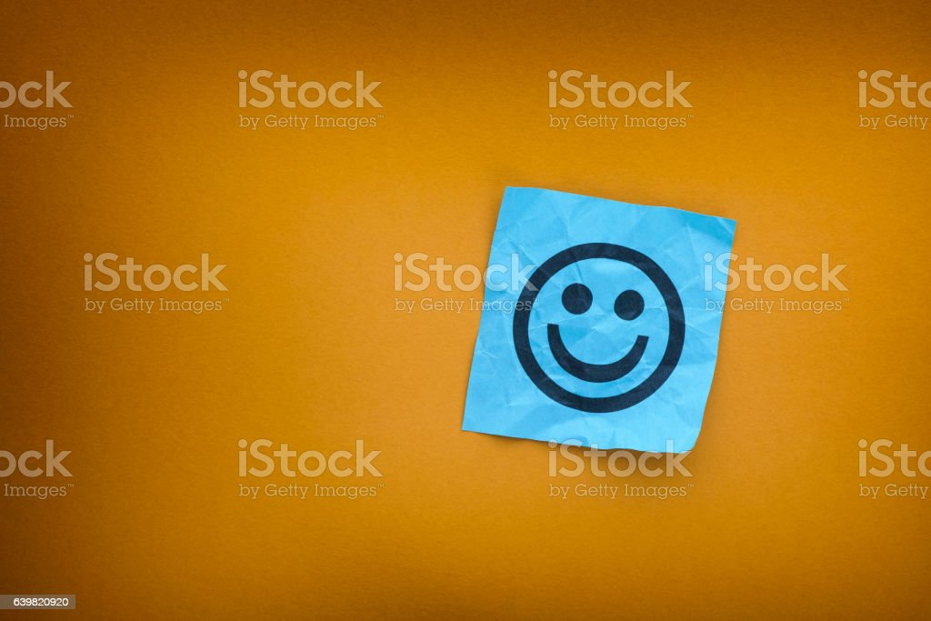 Blue paper note with happy face on a yellow paper background stock photo
