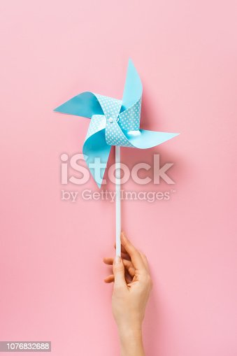 istock Blue paper pinweel on pink background. Energy ecological concept 1076832688