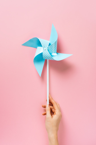 Blue paper pinweel on pink background. Energy ecological concept