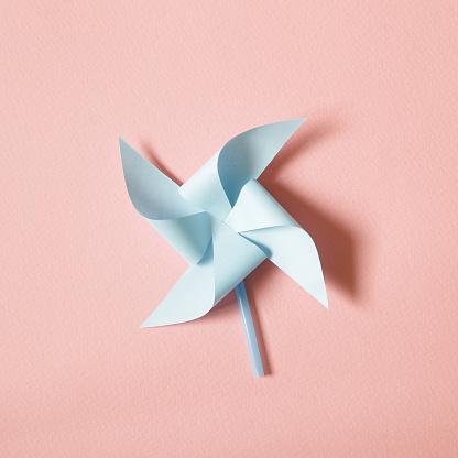 Blue paper pinwheel on pink background