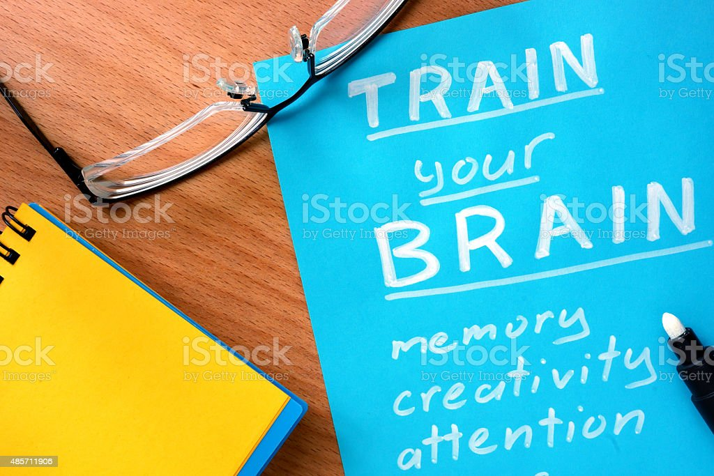 Blue paper with words Train your Brain and glasses. stock photo
