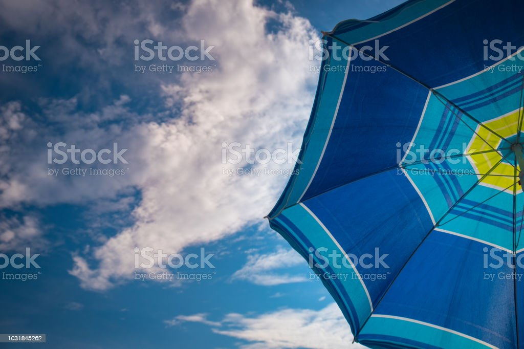 Blue parasol on the blue sky background stock photo