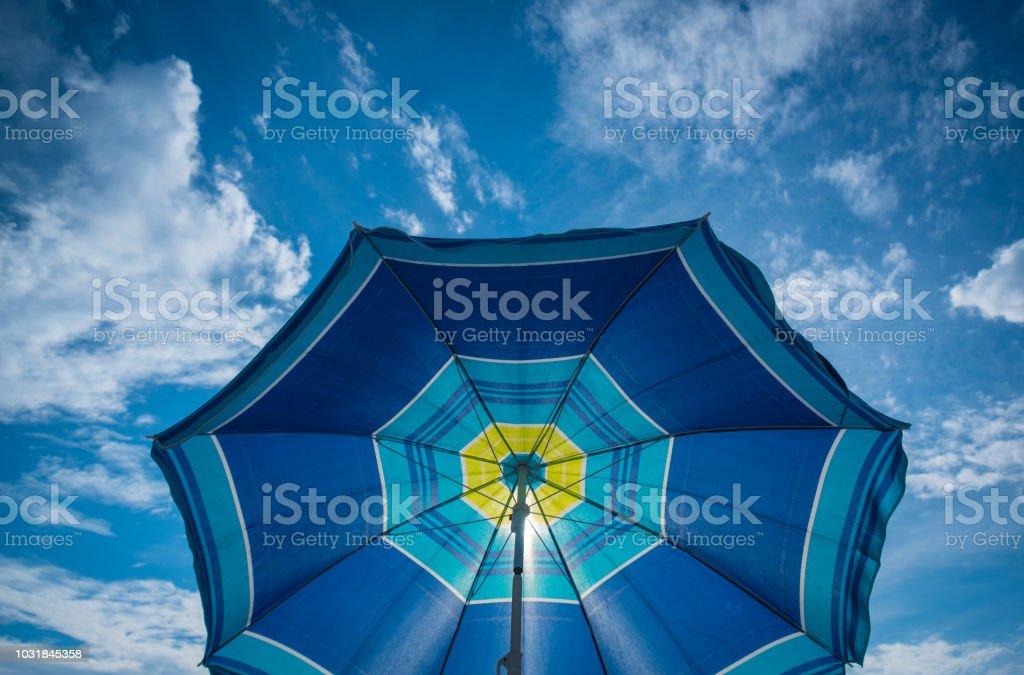 Blue parasol on the blue sky background stock photo