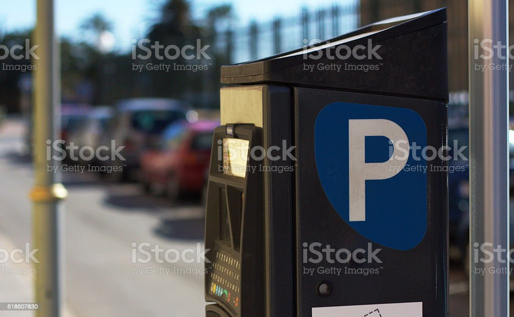 Blue parking sign with blurred cars at the background stock photo