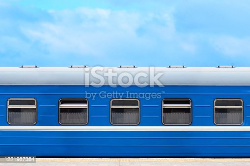 Blue passenger railway wagon on the platform, blue sky in the background