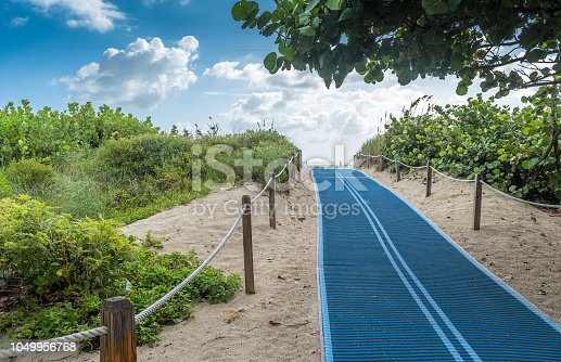 Blue pathway helping people with physical impairment going thru the beach sand.
