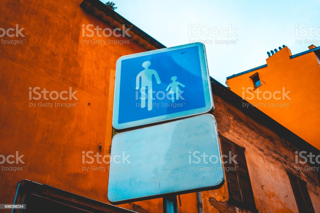 blue pedestrians traffic sign on orange background stock photo