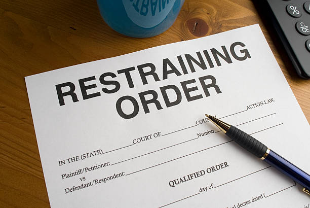 Blue pen laying on a blank restraining order on desk. stock photo