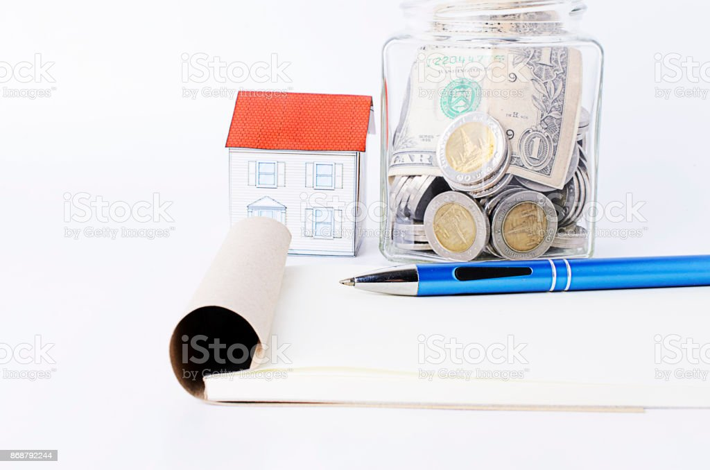 Blue pen with notepad and paper house and bottles glass stock photo