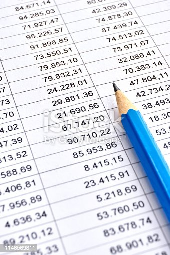 Blue pencil on a sheet of white paper with printed financial numerical data table with columns. Concept for accounting, budget, profit, tax and financial review. Vertical image with selective focus