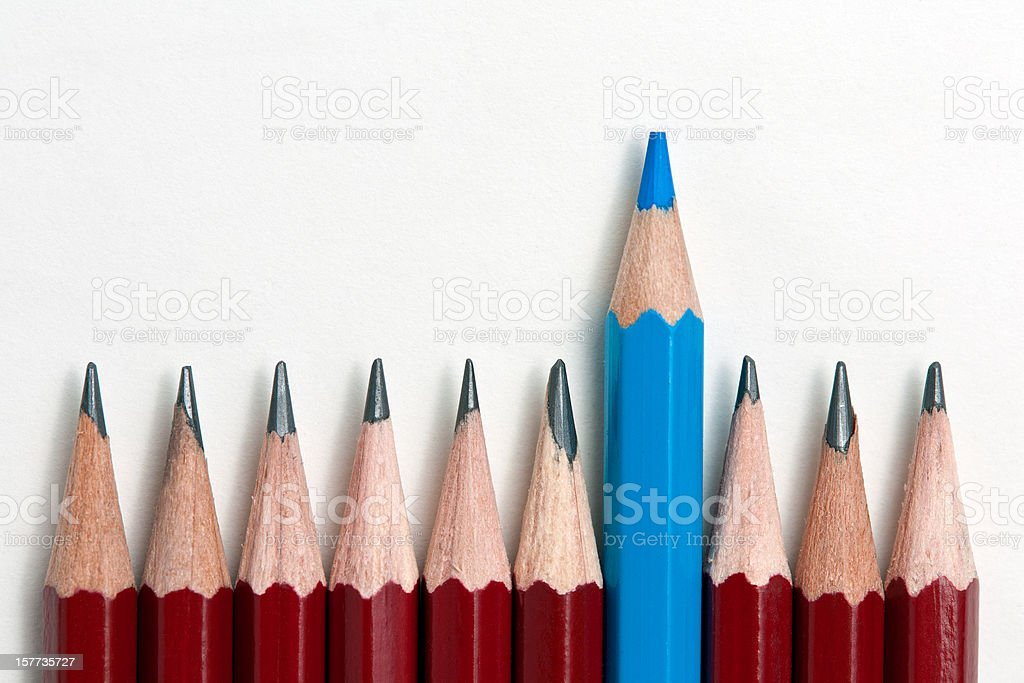 A blue pencil standing out from a row of red pencils stock photo
