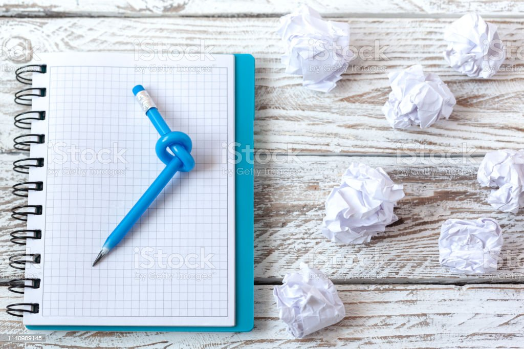 Blue Pencil with knot on writing pad on white wood background.