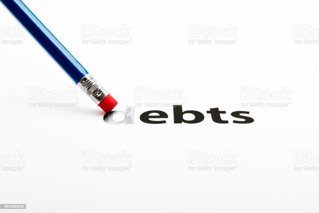 Blue pencil-eraser is rubbing the word DEBTS stock photo