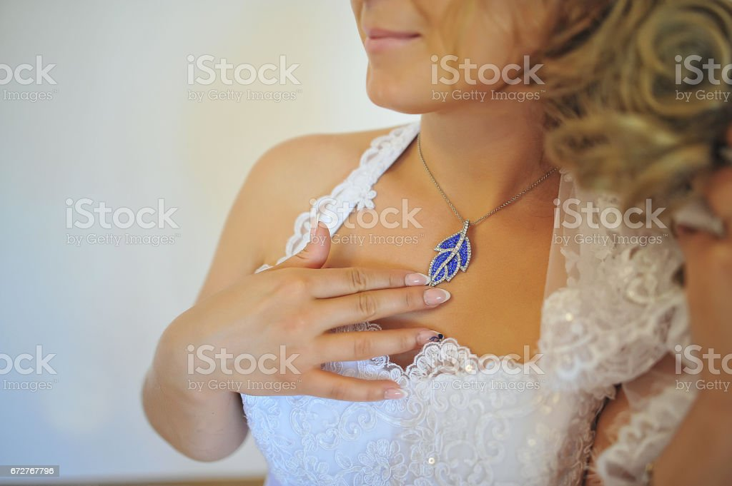 Blue pendant on neck of bride stock photo