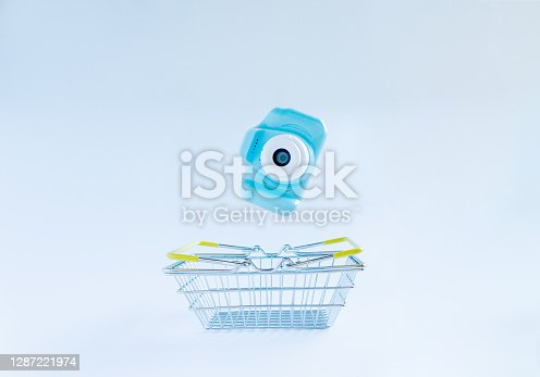 istock Blue photocamera falling in shopping cart on white backround. Electronics and photographic equipment shopping concept 1287221974