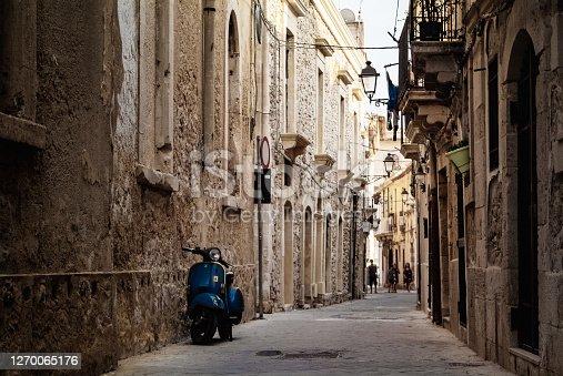 Blue Piaggio Vespa parked at sunset while people walking on the street .Ortigia urban area. Syracuse Siracusa, Sicily Italy, summer season