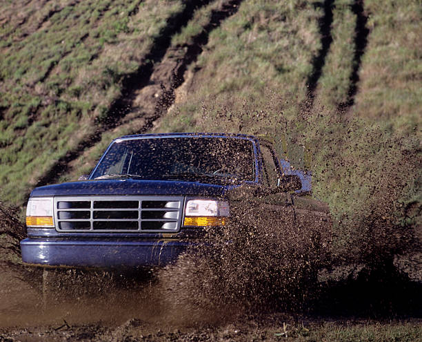 Blue pick up truck driving through a mud puddle stock photo