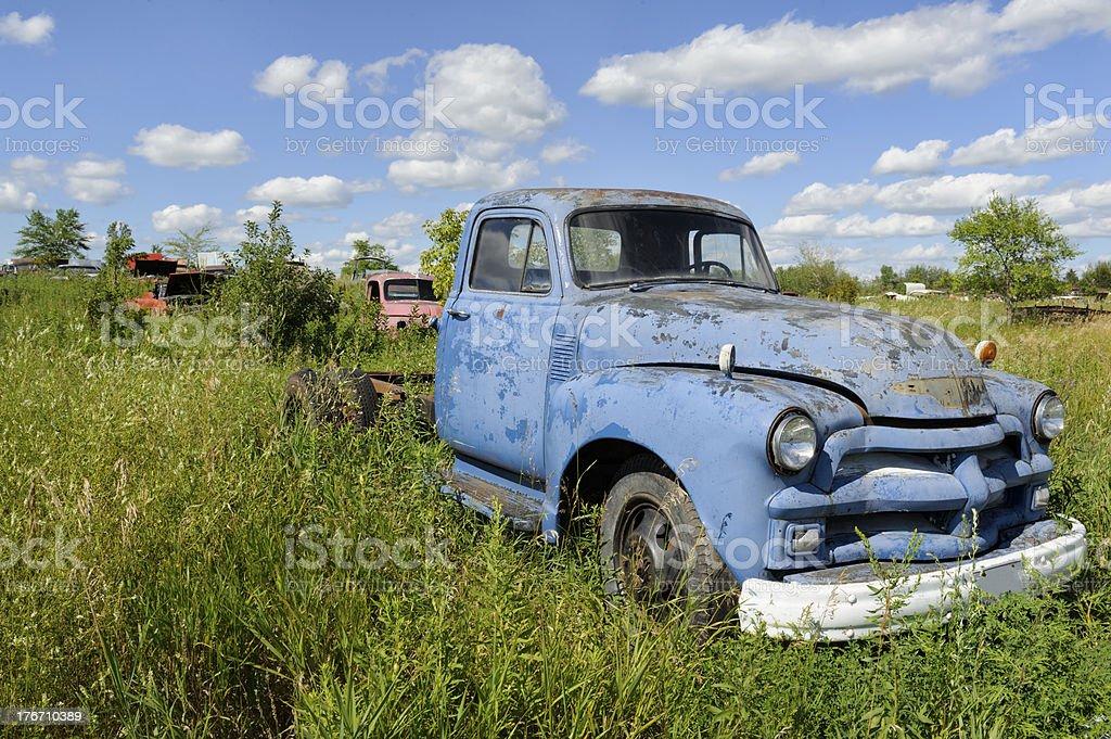 Blue Pickup Truck In Junkyard Under Summer Skies stock photo | iStock