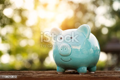 istock Blue piggy bank on wooden table over blurred green bokeh background. Saving money concept 1138210612