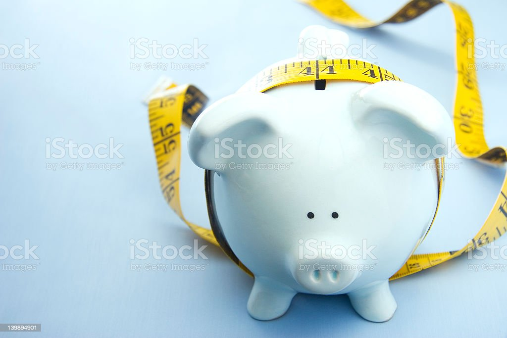 Blue piggy bank with a measuring tape around it Other piggy bank concept: Belt Stock Photo