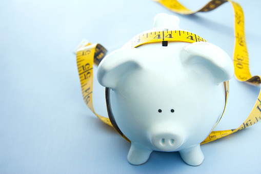 Blue Piggy Bank With A Measuring Tape Around It Stock Photo - Download Image Now