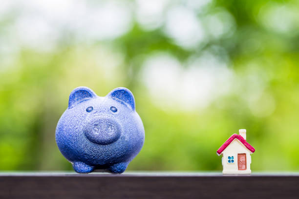 blue piggy bank with tiny home on wooden table over blurred garden bokeh background. stock photo