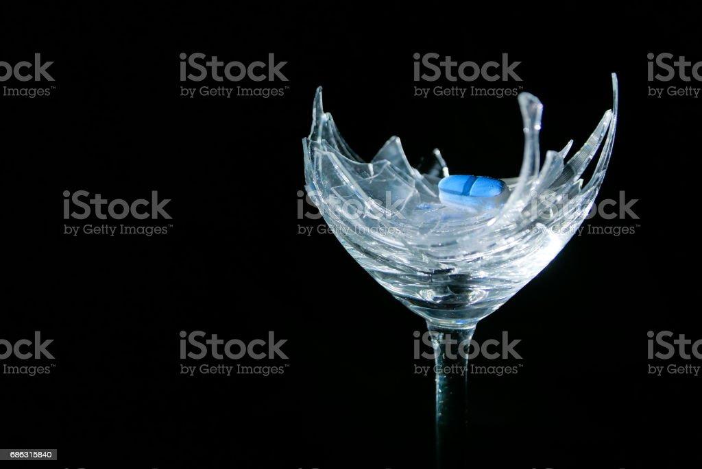 Blue pill on broken glass stock photo