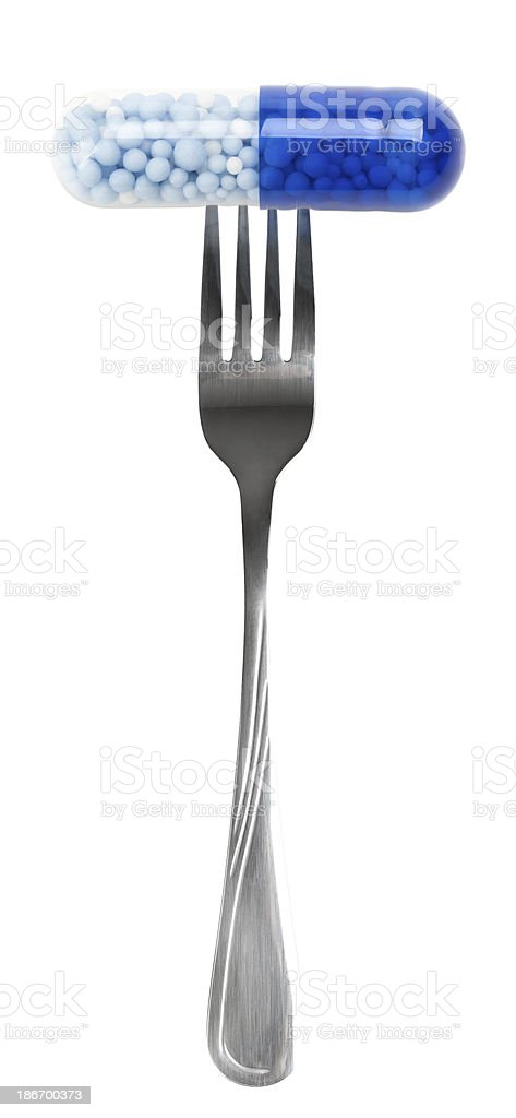 Blue pill on fork royalty-free stock photo