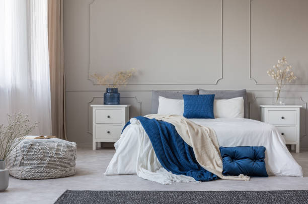 Blue pillow and blanket on white bed in spacious bedroom interior, copy space on empty grey wall – zdjęcie