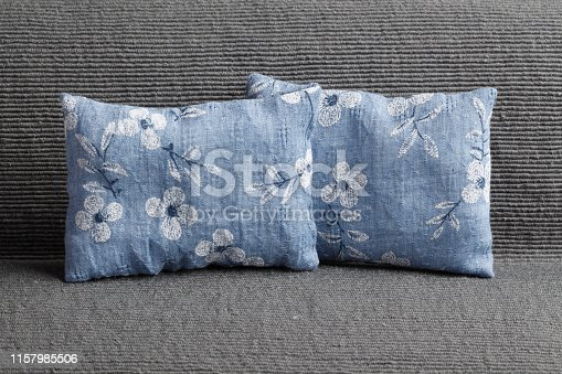 Blue pillows with floral pattern on gray sofa