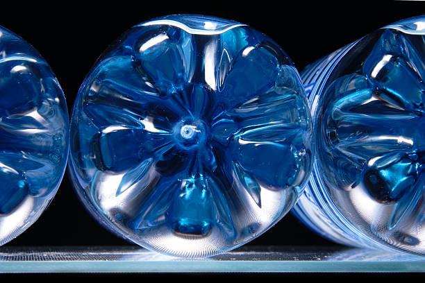 Bouteilles en plastique avec l'eau bleue sur un réfrigérateur intégré - Photo