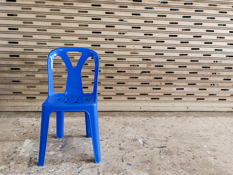 blue plastic chair on cobbled pavement., with copy space for text.