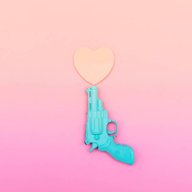 blue plastic gun shoots a heart blue plastic gun shoots a heart shape. minimal. creative concept. gradient color pop musician stock pictures, royalty-free photos & images