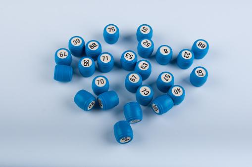 Blue plastic kegs for bingo lay on white background