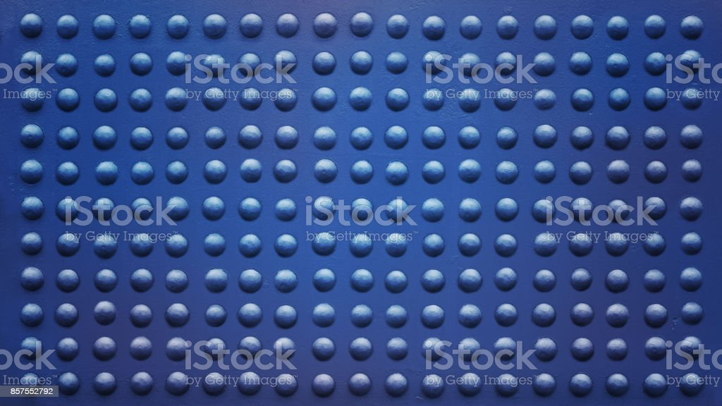 blue plate full of rivets stock photo