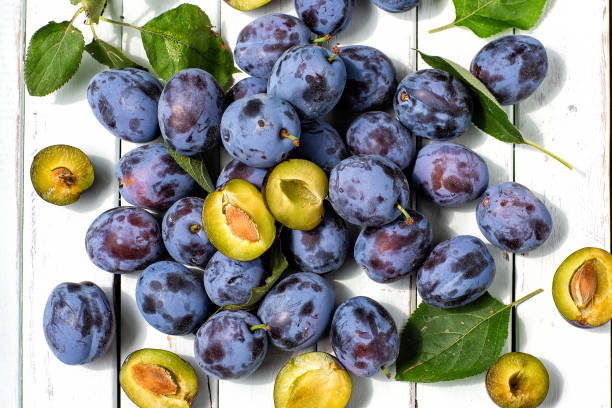 blue plums on light wooden background.fruits.the view from the top stock photo