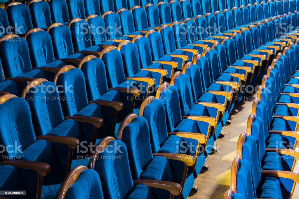 Blue plush chairs with wooden armrests in the auditorium. Empty...