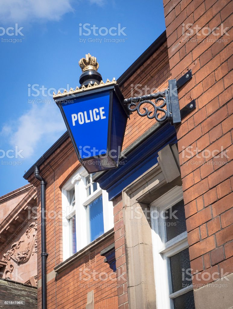 Blue Police Station Signage on Brown Stone Building Background stock photo
