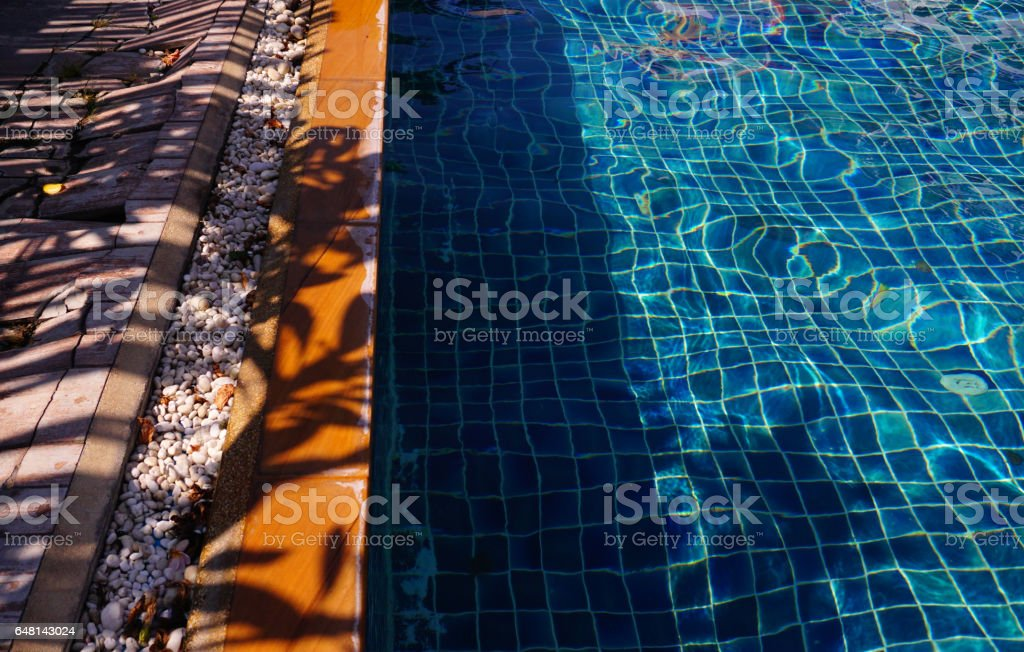 Blue pool water with sun reflections background stock photo