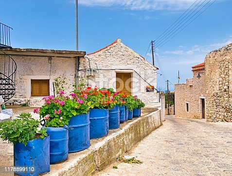 Blue pots with colorful red and pink flowers in front of a stone village house in Laconia, Peloponnese, Greece.
