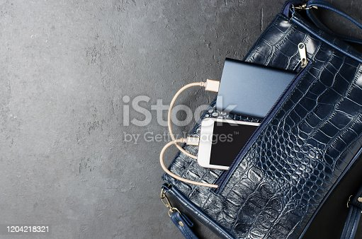 istock Blue Power Bank and telephone in the women's bag. Dark grey concrete background. Copy space 1204218321