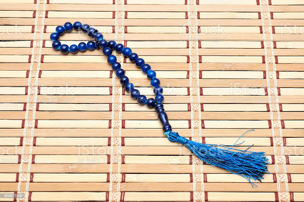 Blue rosary on wooden mat stock photo