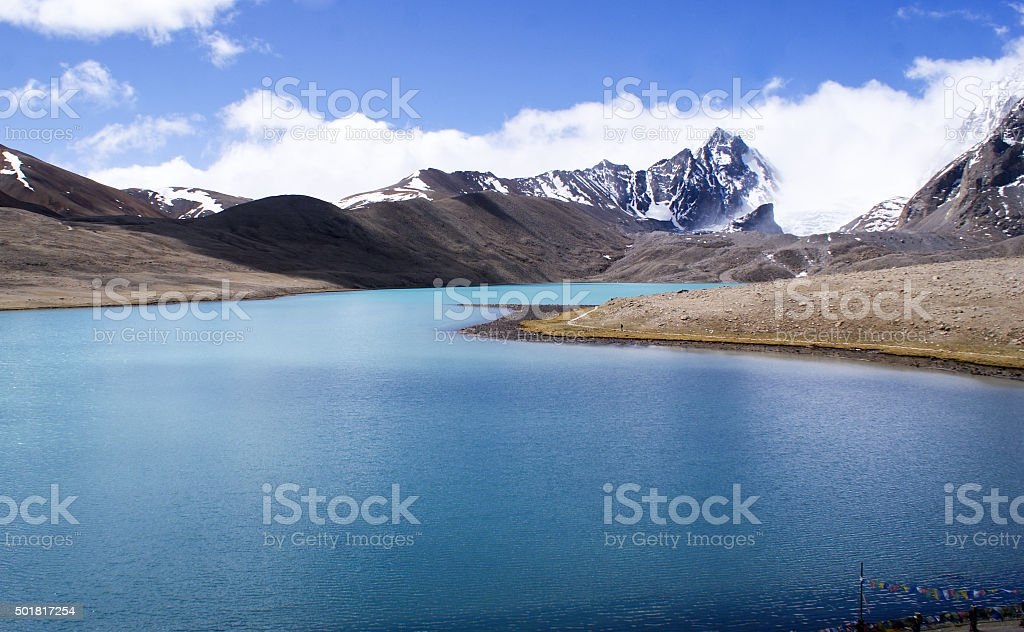 Blue pristine lake surrounded by mighty Himalayan peaks stock photo