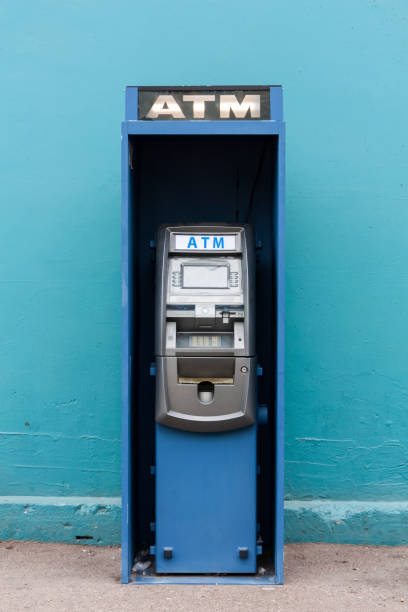 blue public ATM, Automated Teller Machine on street in front of wall stock photo